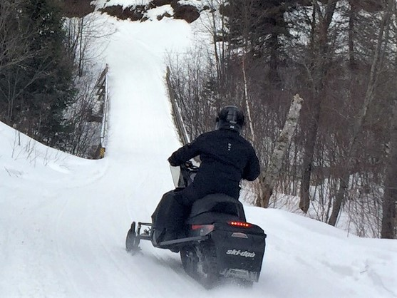 Snowmobile single rider driving away